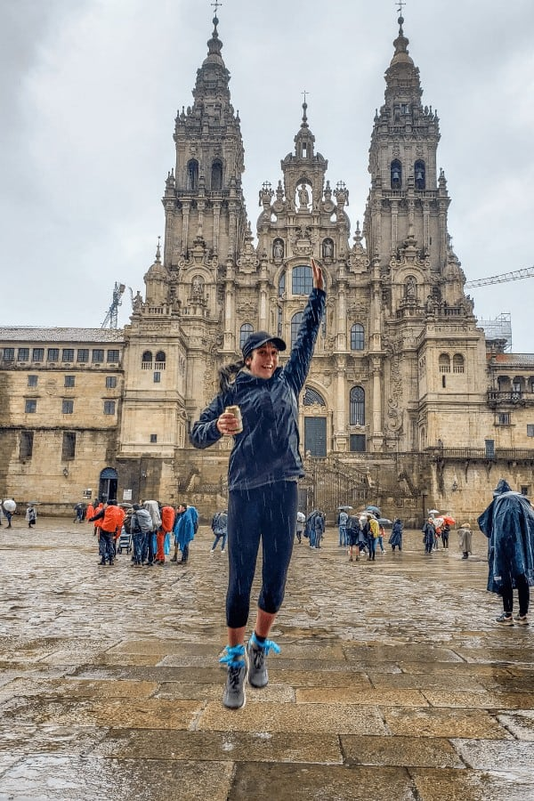 Female pilgrim in rain jacket celebrating finishing the Portuguese Camino de Santiago. Check out this guide to find out what it's really like to walk Porto to Santiago de Compostela?